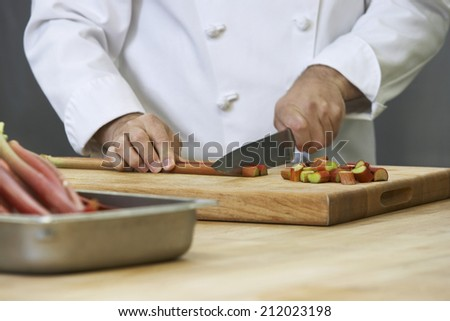 Closeup midsection of a chef chopping rhubarb - stock photo