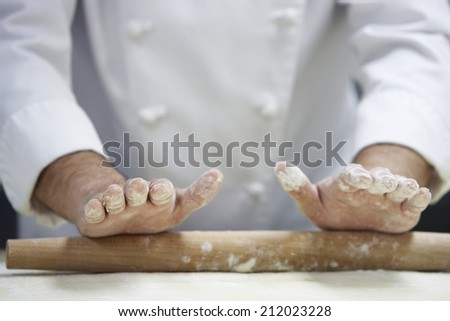 Closeup midsection of a chef rolling dough with rollingpin - stock photo