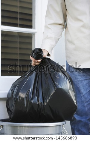 Closeup midsection of a man putting garbage bag into trash can - stock photo
