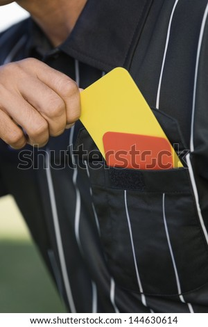 Closeup midsection of a referee taking card from his pocket - stock photo