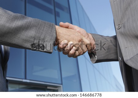 Closeup midsection of businessmen shaking hands against office building - stock photo