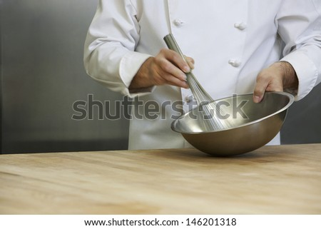 Closeup midsection of hands mixing ingredients in a bowl - stock photo