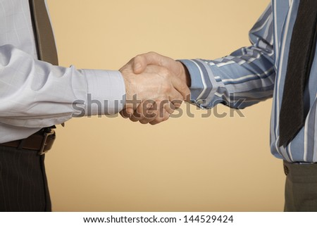 Closeup midsection of two businessmen shaking hands against colored background - stock photo