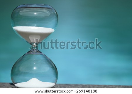 Closeup modern hourglass sits on poolside -- sand trickling through the bulbs of a crystal sand glass. every second counts. symbol of time. summer countdown. - stock photo
