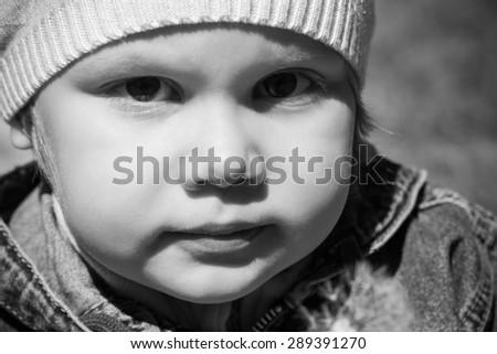 Closeup monochrome portrait of small Caucasian girl on the walk, outdoor photo - stock photo