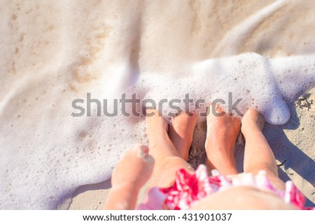 Closeup mother and kid feet on white sand beach