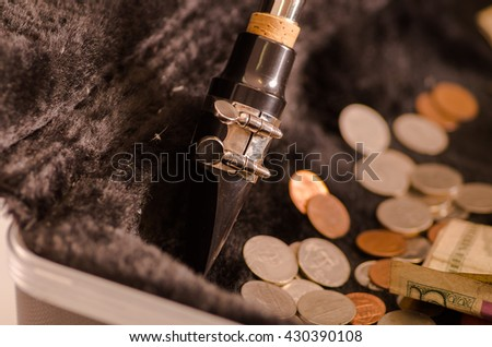 Closeup mouthpiece saxophone lying across open instrumental casing with black velvet interior and pile of money inside - stock photo