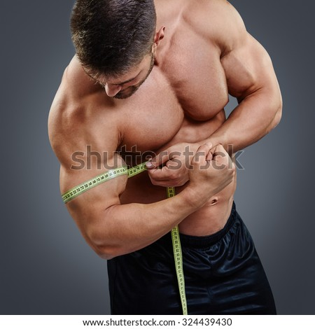 Closeup Muscular bodybuilder measuring biceps with tape measure isolated over gray background. Bodybuilder tries to measure gain in bicep by himself. - stock photo