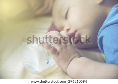 closeup newborn  Baby hand and finger . Baby  holding bottle while sleeping and drinking milk from bottle - stock photo