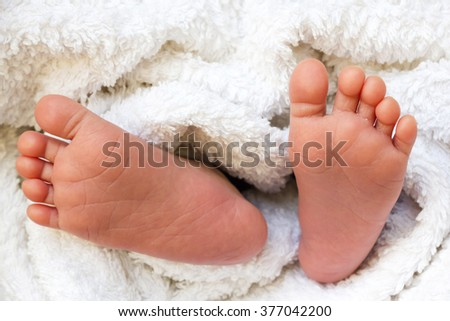 Closeup newborn foot with white cloth. - stock photo
