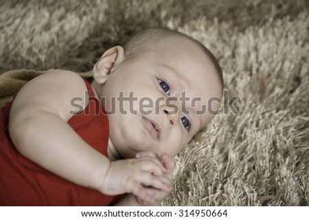 closeup of a baby boy lying on his side  a brown carpet, - stock photo