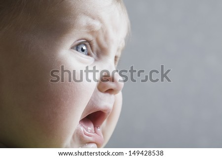Closeup of a baby girl crying against gray background - stock photo