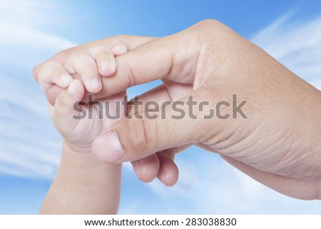 Closeup of a baby hand grasping father's finger, shot outdoors under clear sky - stock photo