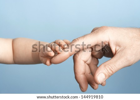 Closeup of a baby holding man's finger against blue background - stock photo