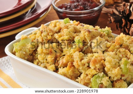 Closeup of a baking dish of cornbread stuffing with celery and turkey bits - stock photo