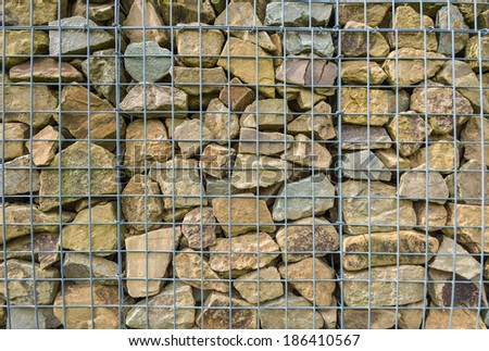 Closeup of a barrier built of small pieces of rock behind a fence of metallic mesh