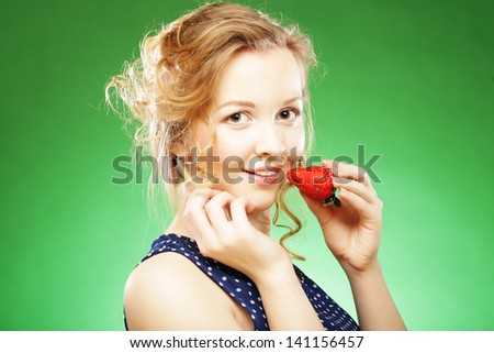 Closeup of a beautiful blond  holding a strawberry