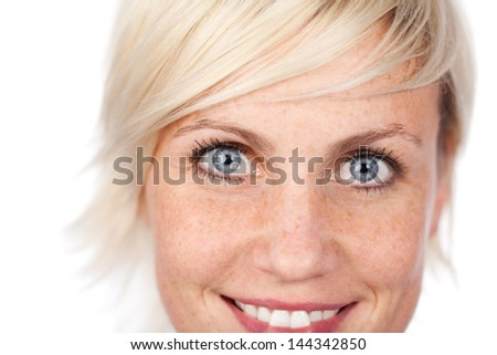 Closeup of a beautiful blue eyed woman looking at camera against white background - stock photo