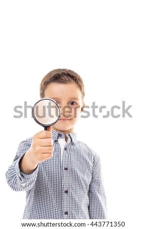 Closeup of a beautiful child looking through a magnifying glass loop over white  - stock photo