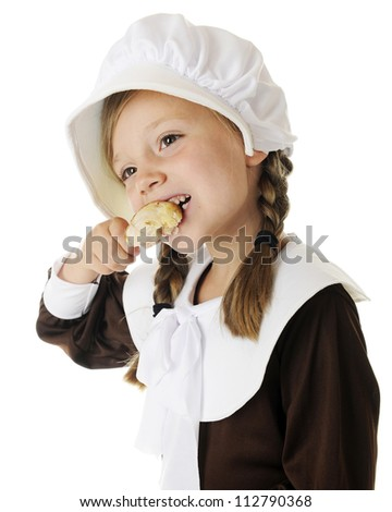 Closeup of a beautiful elementary Pilgrim girl happily enjoying a small drumstick.  On a white background. - stock photo