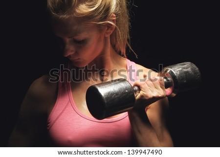 Closeup of a beautiful fitness woman lifting weights - stock photo