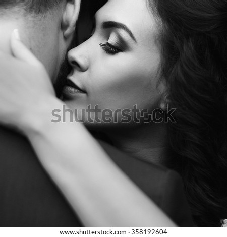 Closeup of a beautiful, happy bride hugging handsome groom with her eyes closed b&w - stock photo