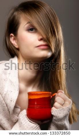 Closeup of a beautiful thoughtful sad woman holding a nice red mug of warm beverage gray background - stock photo