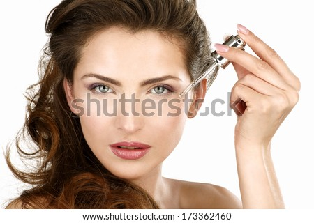 Closeup of a beautiful woman applying a beauty treatment on white - stock photo