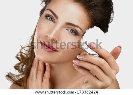Closeup of a beautiful woman checking her makeup in the mirror on white - stock photo