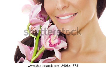 Closeup of a beautiful woman smile with pink orchids. Isolated stock image on white. Beauty  and skincare concept.