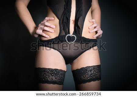 Closeup of a beautiful young woman in black lingerie and stockings, high resolution photo in front of black studio background - stock photo