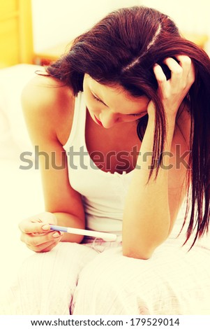 closeup of a beautiful young woman in the bedroom worrying because of the pregnancy test result. - stock photo