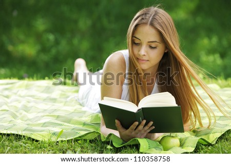 Closeup of a beautiful young woman reading book at park