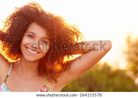 Closeup of a beautiful young woman with a sunset behind her - stock photo