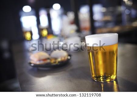 closeup of a beer glass in a bar - stock photo