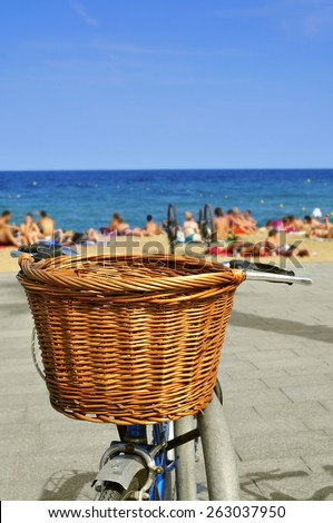closeup of a bicycle with a wicker basket parked in the seafront with blurred people on the beach in the background - stock photo