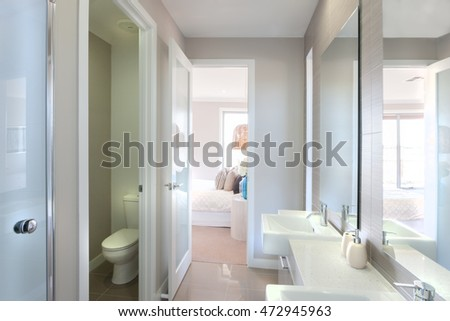 Closeup of a big mirrors on the wall near to the tap and white sink with liquid soap bottle, the toilet bowl isolated in a room. There is a way to the bedroom from the washroom