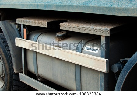 Closeup of a biodiesel tank of a large excavation truck covered with dirt - stock photo