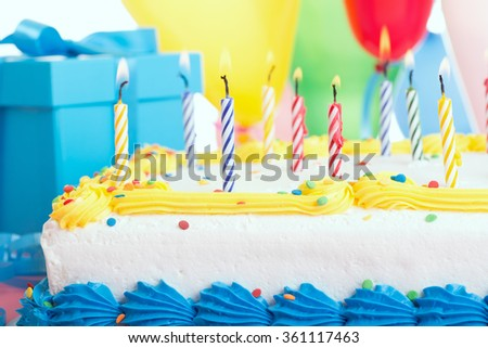 Closeup of a birthday cake with burning candles