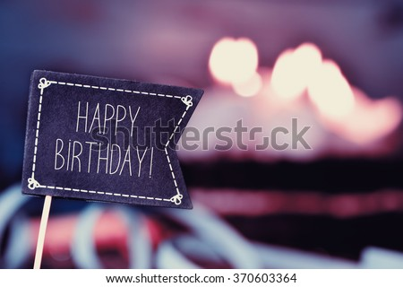 closeup of a black flag-shaped signboard with the text happy birthday, and a birthday cake with lit candles in the background - stock photo