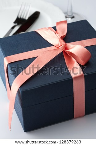 Closeup of a black gift box tied with a decorative red ribbon and bow for that special loved one to celebrate a birthday, anniversary Christmas or Valentines