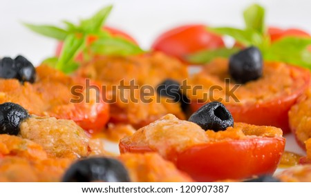 closeup of a black olives on a stuffed tomato
