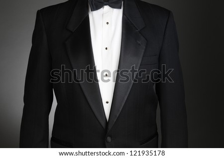 Closeup of a Black Tuxedo Jacket. Torso only on a light to dark gray background. Horizontal format. - stock photo
