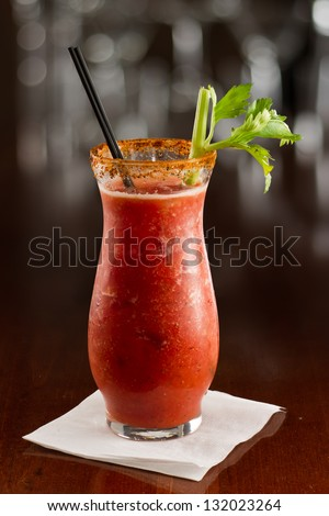 closeup of a bloody mary cocktail garnished with a celery sick isolated on a busy bar top - stock photo