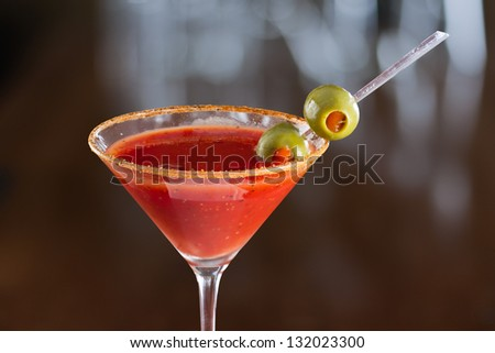 closeup of a bloody mary cocktail garnished with olives isolated on a busy bar top - stock photo