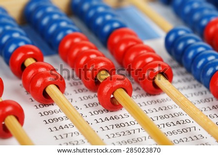 closeup of a blue and red abacus on sheet with numbers - stock photo