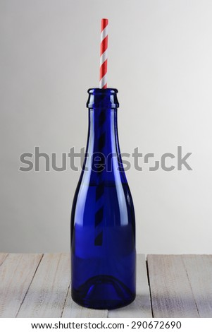 Closeup of a blue bottle with a red striped drinking straw. The bottle is on a rustic wood table with a light to dark gray background. - stock photo