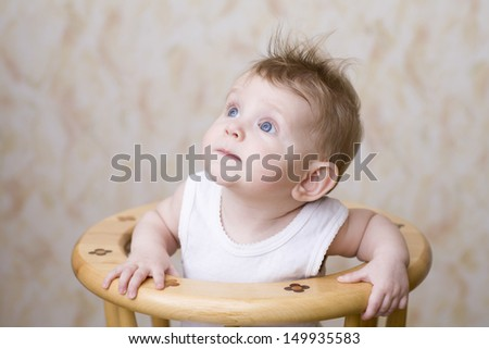 Closeup of a blue eyed baby boy on high chair looking up