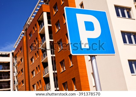 Closeup of a blue park sign, brown building in background - stock photo