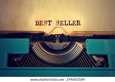 closeup of a blue retro typewritter and the text best seller written with it in a yellowish foil - stock photo
